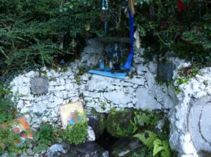 "Skour Well at Lough Hyne in Ireland with icons and prayer ""rags"" hanging from overhangingsacred tree"