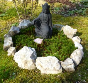 A circle of milky quartz stone in moss around a black lava Kwan Yin.