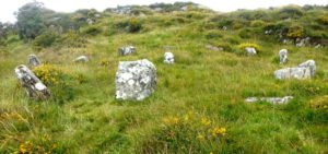 A stone circle set in grass on a hillside in Ireland.